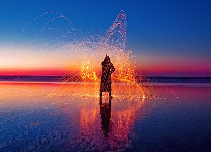 Figure standing on water with lights flashing around