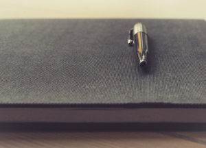 Metal pen on-top of a notebook