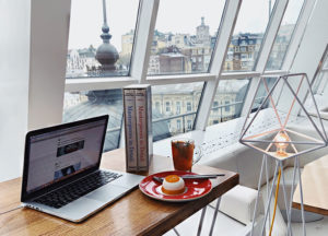 Fancy desk with laptop overlooking an old city