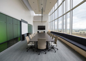 Empty conference room table with open windows